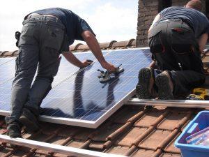 Men installing solar panels on roof of family home