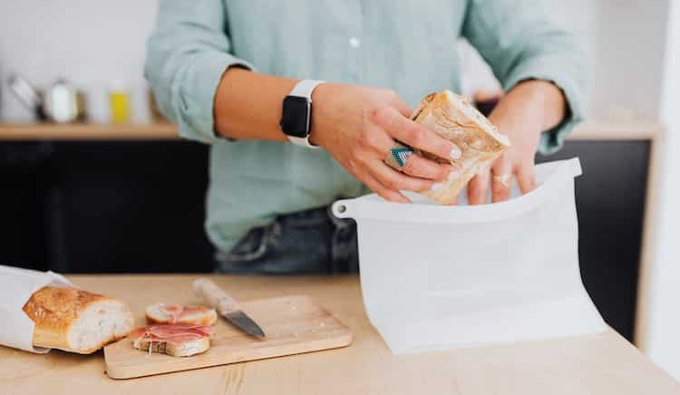woman packing bread into a silicone storage bag