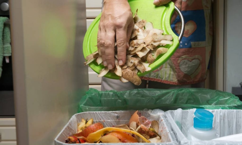 a person throwing away vegetable scraps