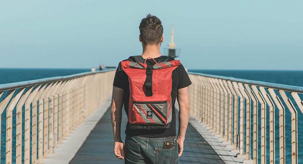 a man wearing a travel bag made of sustainable leather alternatives