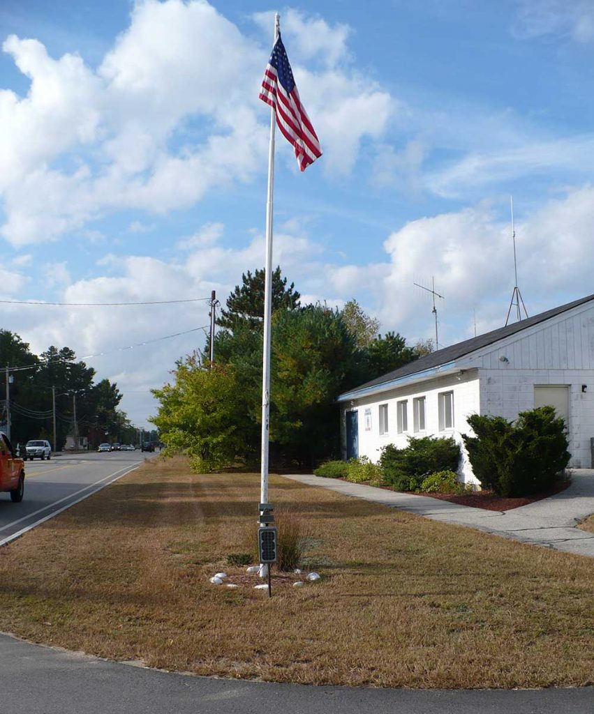 a flag on a pole with a small solar panel at the bottom to power flagpole light